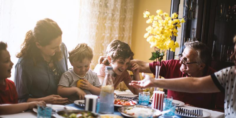 family at dinner table laughing